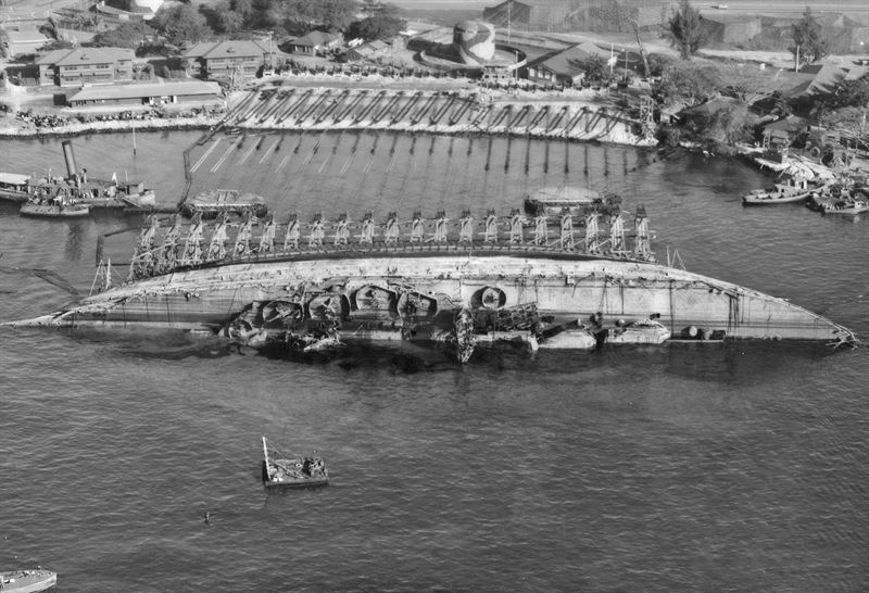 USS Oklahoma salvage. Aerial view toward shore with ship in 90 degree position. Wells Battleship