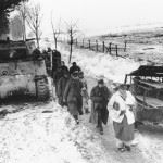 German captives walk past a disabled tank as they are led into captivity by U.S. troops, on Jan. 25, 1945, north of Foy, Belgium, in the final days of the Battle of the Bulge.