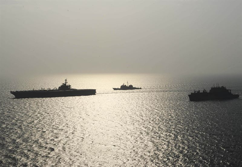 The aircraft carrier USS Theodore Roosevelt (CVN 71) transits alongside the guided-missile cruiser USS Normandy (CG 60) and the Military Sealift Command dry cargo and ammunition ship USNS Carl Brashear (T-AKE 7) during a replenishment-at-sea. Theodore Roosevelt is deployed in the U.S. 5th Fleet area of operations supporting Operation Inherent Resolve, strike operations in Iraq and Syria as directed, maritime security operations and theater security cooperation efforts in the region. (U.S. Navy photo by Mass Communication Specialist 3rd Class Taylor L. Jackson)