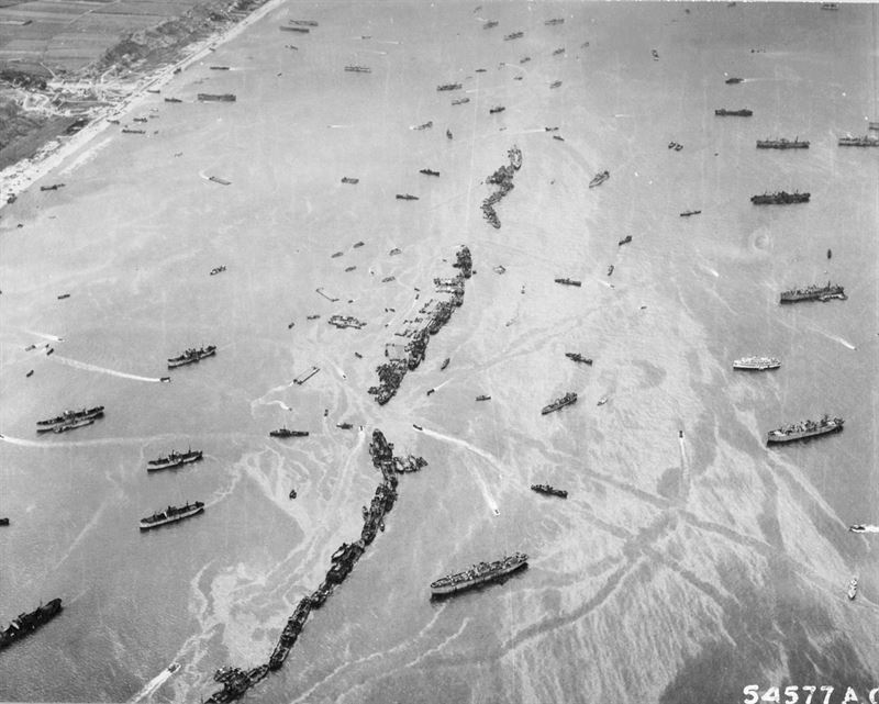 """Omaha Beach""American Liberty ships were deliberately scuttled off the beaches to provide makeshift breakwaters during the early days of the invasion somewhere in France. This scene shows 13 Liberty ships formed into a protecting screen for the vessels unloading on the beach. (Credits: U.S. Army)"