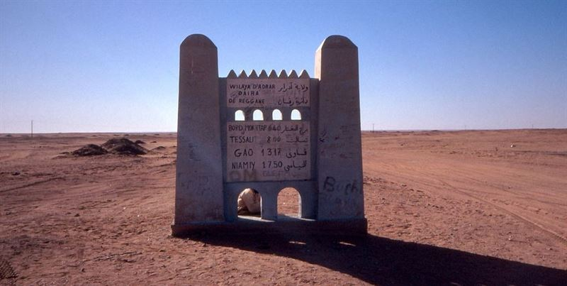A road sign south of Reggane. The town lies within the Sahara Desert, on the edge of an oasis. Algeria is attempting to bring more tourism to the area.